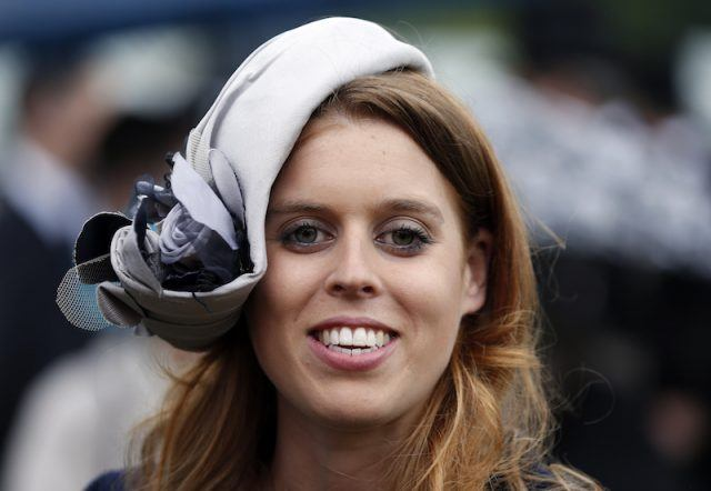 Princess Beatrice smiling while wearing a blue headpiece.
