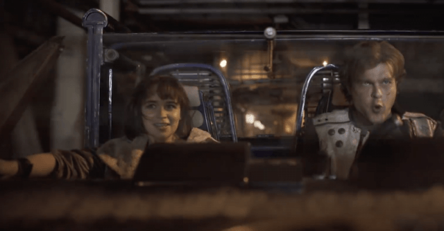 Qi'ra and Han riding in a vehicle.