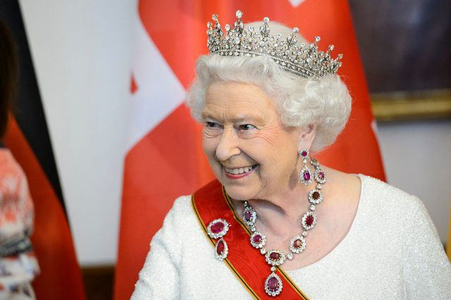 Queen Elizabeth II smiles while wearing a tiara and red sash.