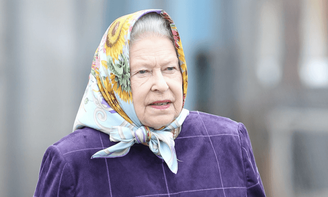 Queen Elizabeth walks with a scarf wrapped around her head.