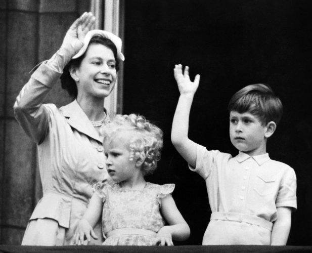 Queen Elizabeth with Prince Phillip and Princess Anne waving from a balcony.
