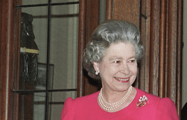 Queen Elizabeth smiling while wearing pearls and a pink dress.