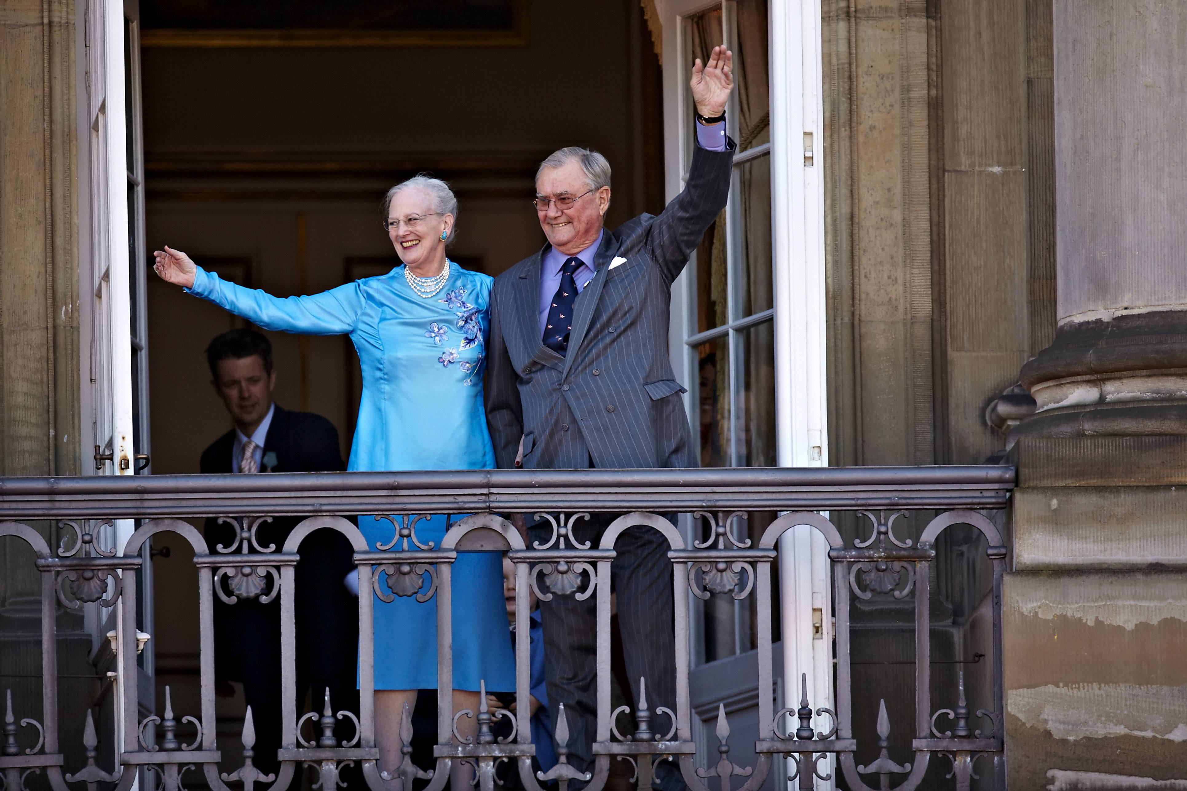 Queen Margrethe and Prince Henrik of Denmark waving from a balcony