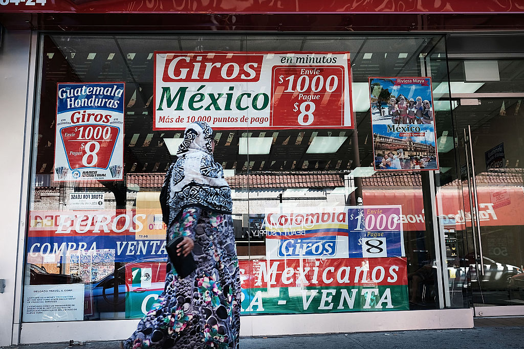 A woman walks by a store specializing in phone calls and travel to Latin America in the ethnically diverse neighborhood of Queens