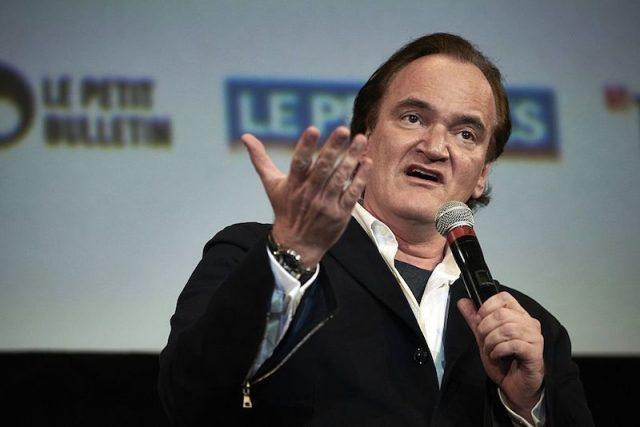 Quentin Tarantino holding a microphone and speaking on stage.