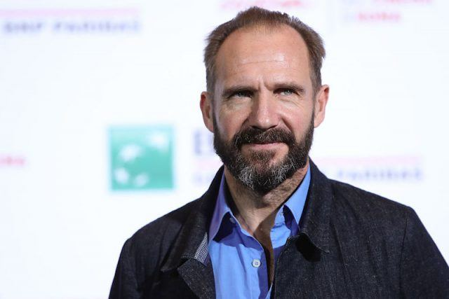 Ralph Fiennes posing in a blue shirt and black jacket.