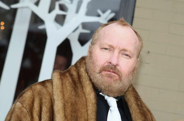 Randy Quaid in a fur jacket.