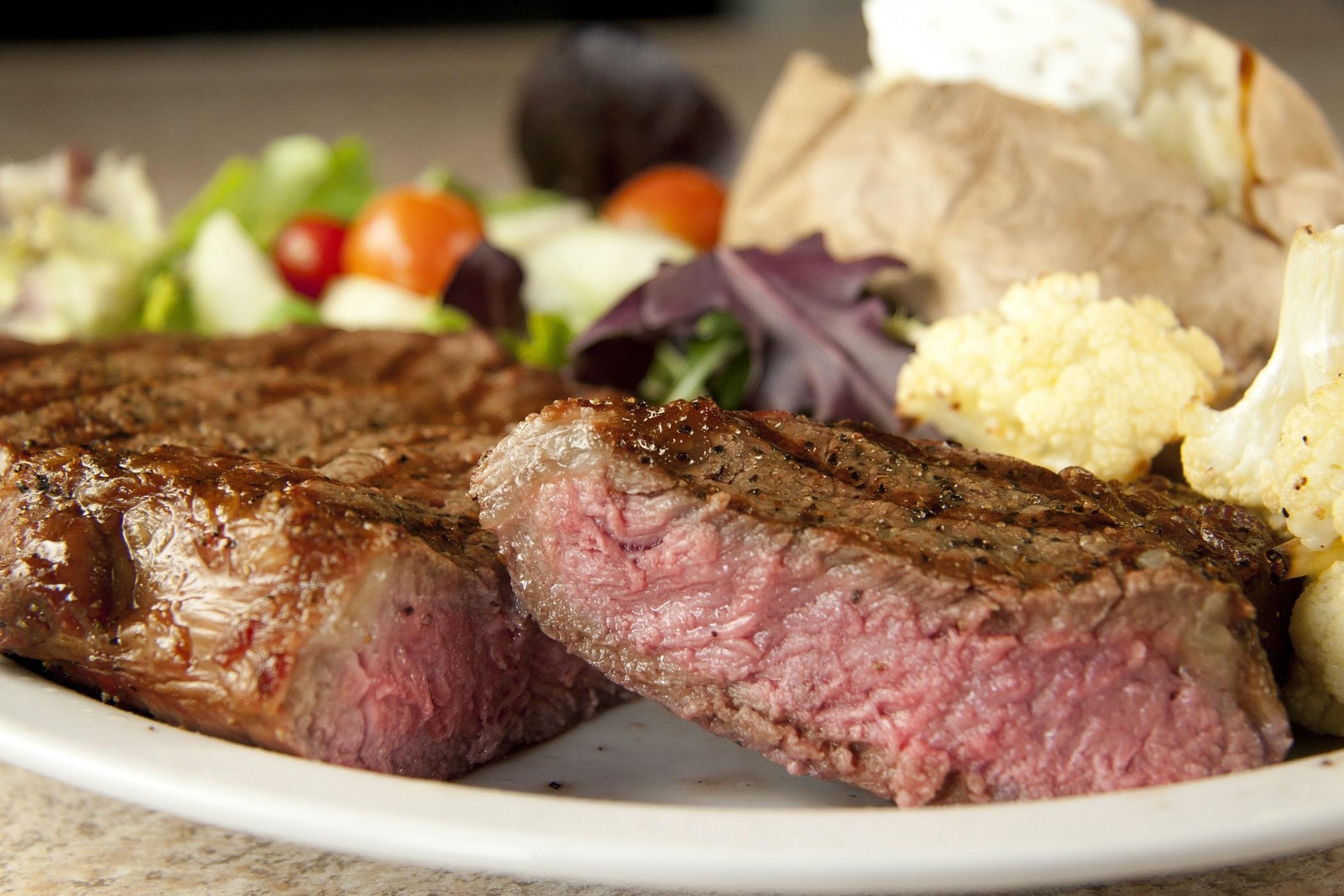 Rib eye steak with baked potato and salad