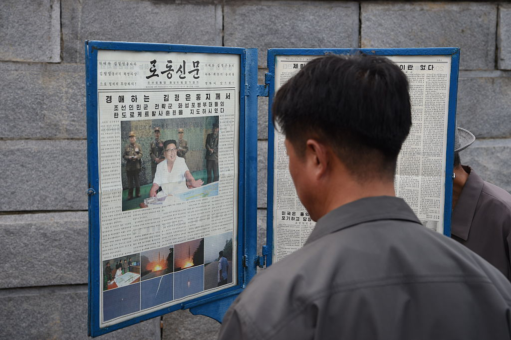 Man reading North Korean newspaper Rodong Sinmun