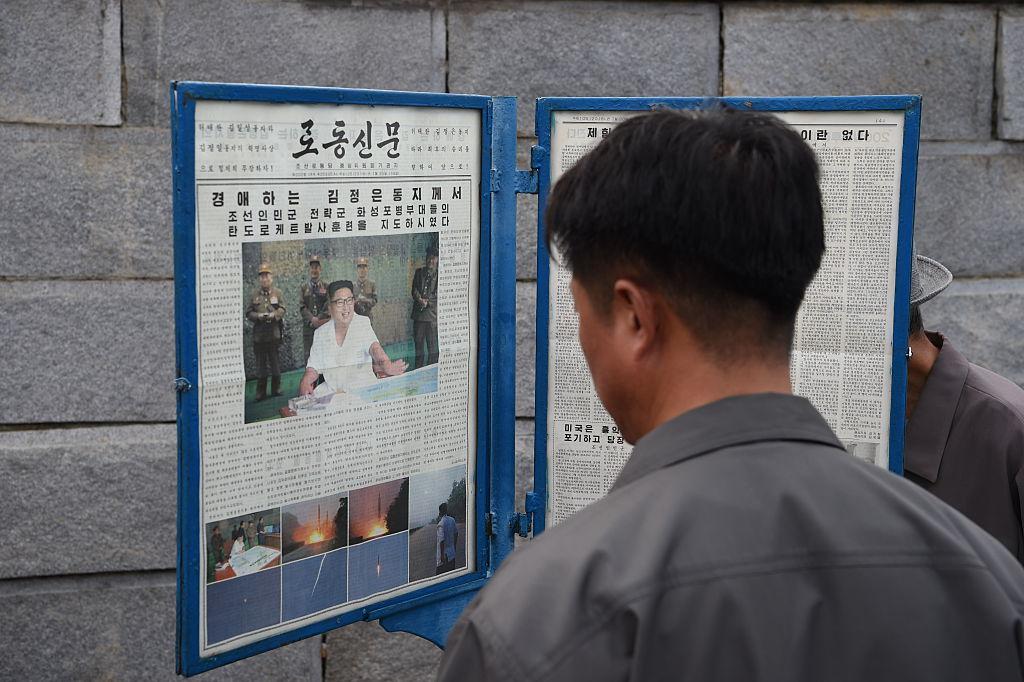 Man reading North Korean newspaper Rodong Sinmun