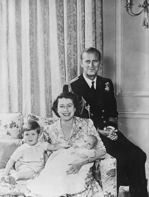 Queen Elizabeth smiling as she holds Prince Anne and Prince Charles. Prince Phillip sits behind her.