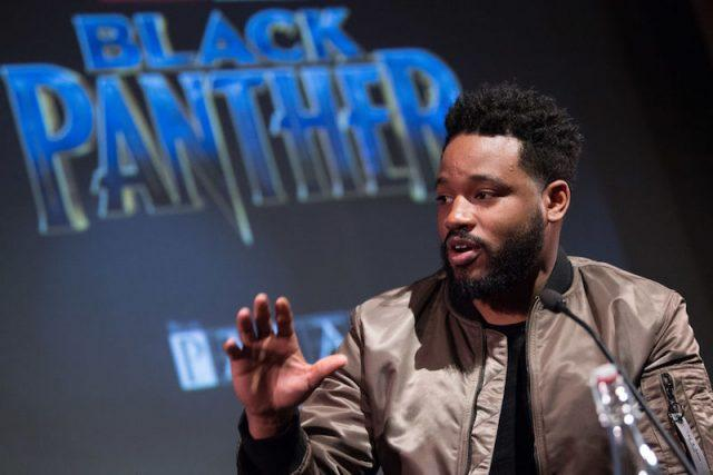Ryan Coogler speaking in front of a screen featuring the 'Black Panther' logo.