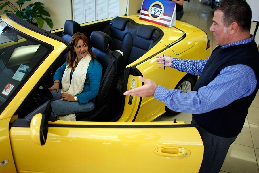 Freddy Melayes shows a new Saab to Karen Cossio at the Deel Saab dealership