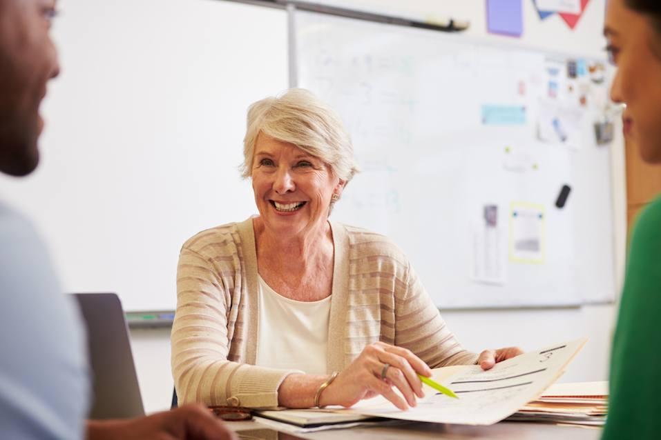 Senior teacher at desk talking to adult education students