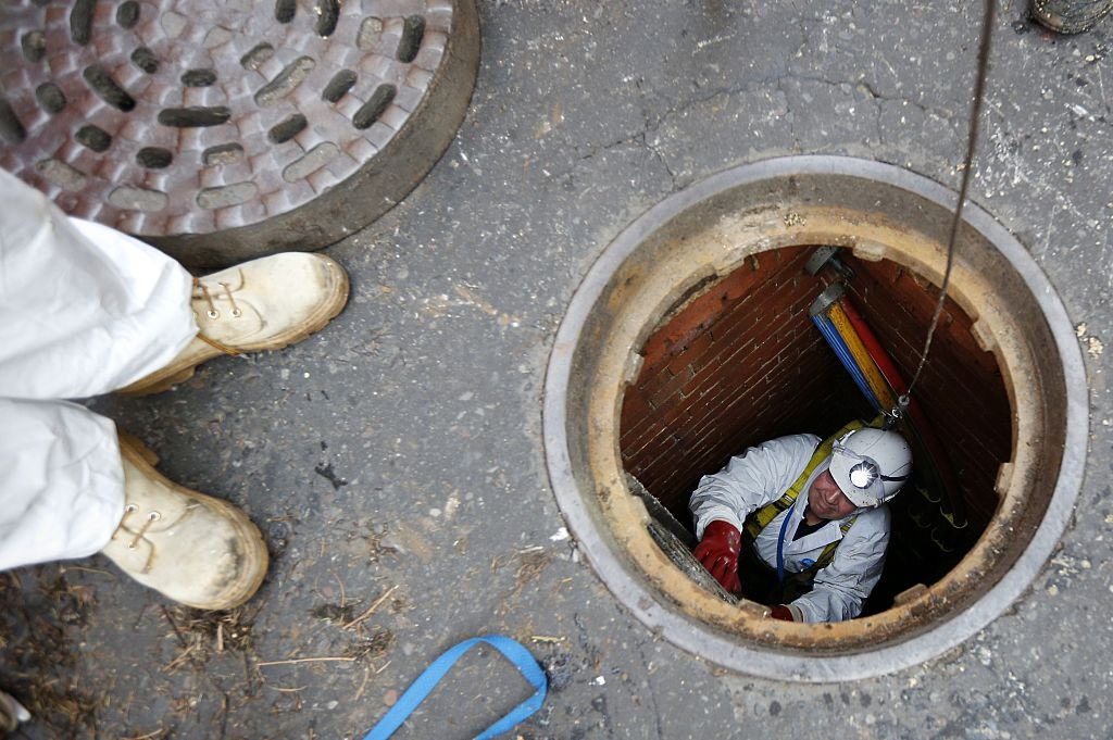 London sewer worker descending into manhole