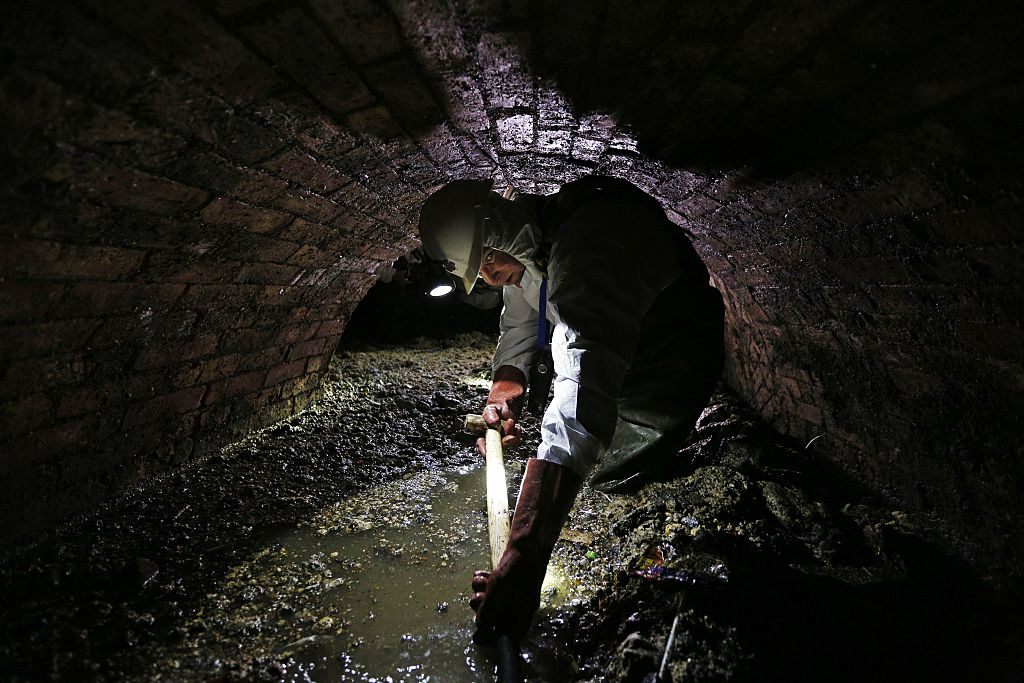 Sewer worker in London sewer with fatberg