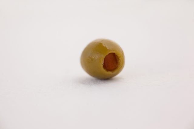 Single green olive on table