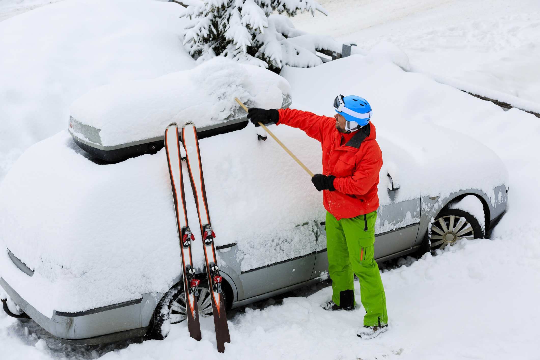 A man clearing snow off his car to go skiing