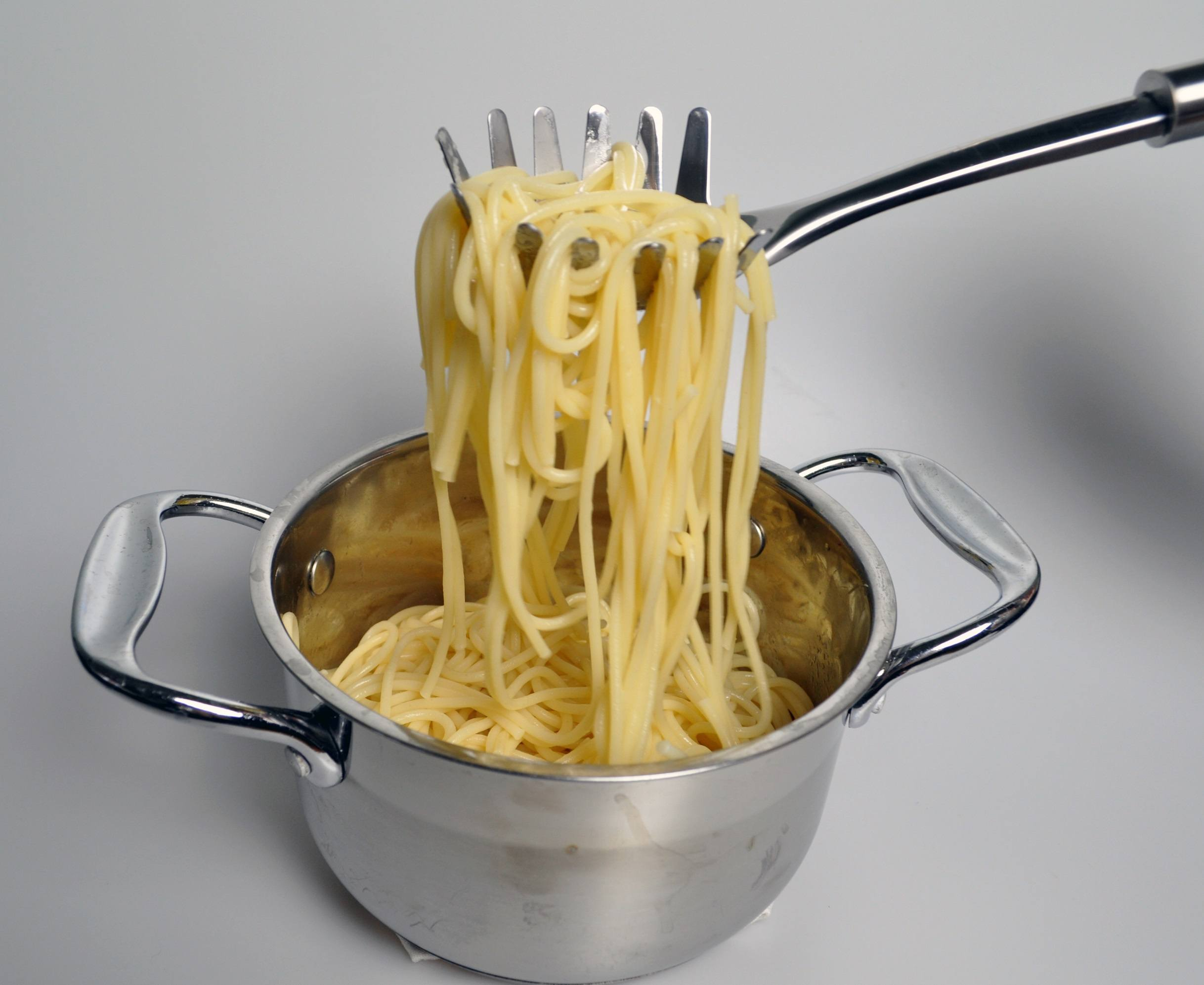 boiled spaghetti in a saucepan, in a spoon for spaghetti