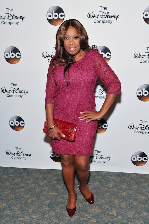 Star Jones smiles while wearing a purple dress.