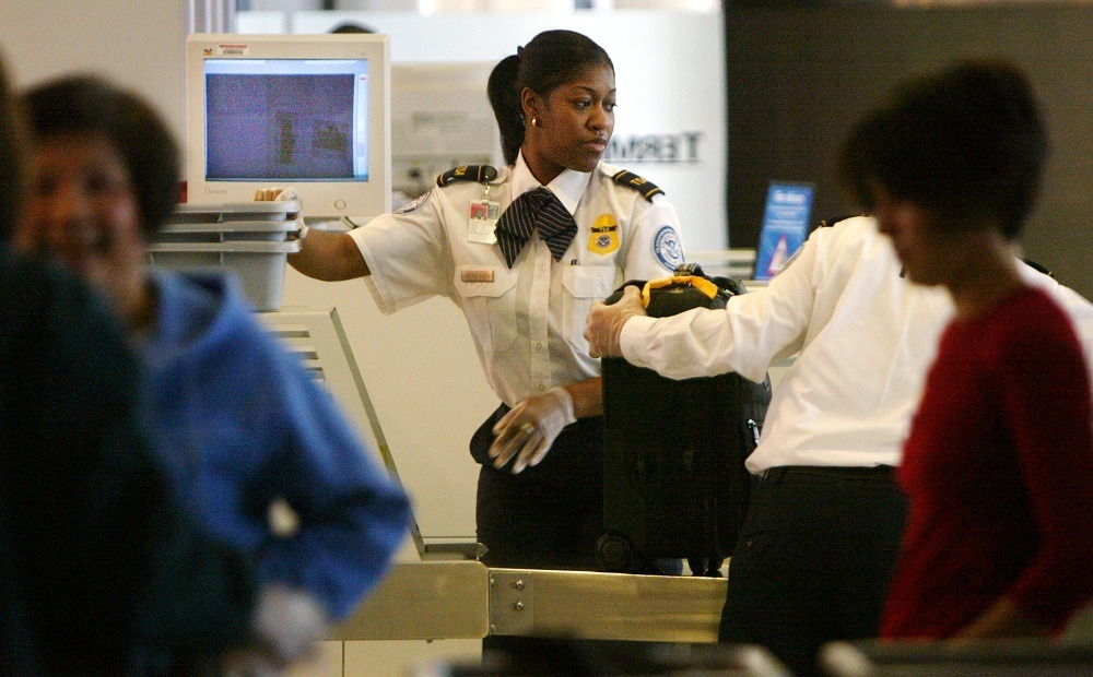 A Transportation Safety Administration (TSA) officer screens carry-on baggage at a passenger