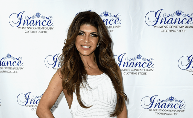 Teresa smiling and posing in a white and silver dress on a red carpet.