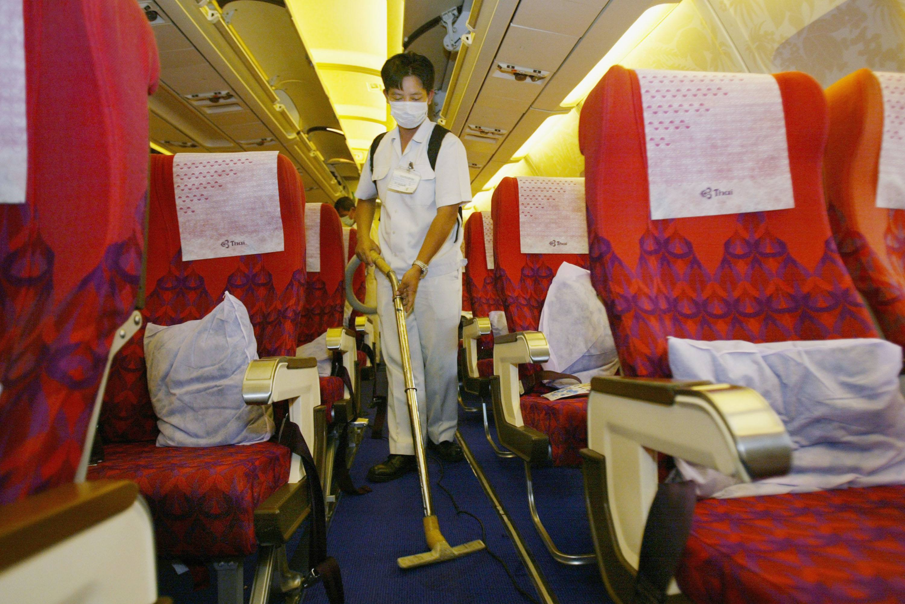 A Thai airlines staff worker cleans the aircraft wearing a surgical mask