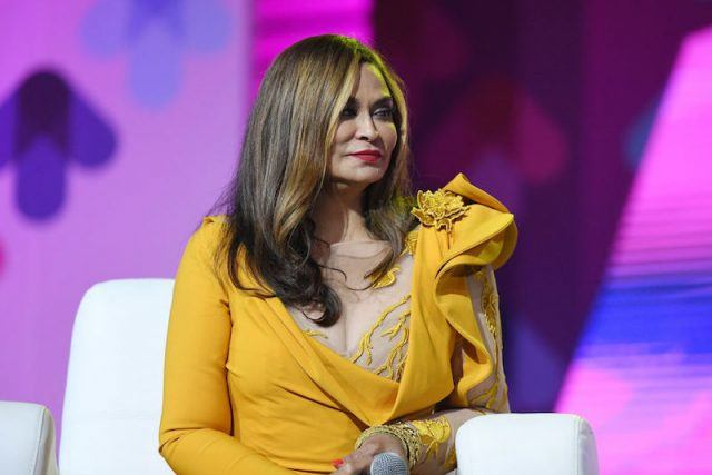 Tina Knowles Lawson sits on a white couch during an on-stage interview.