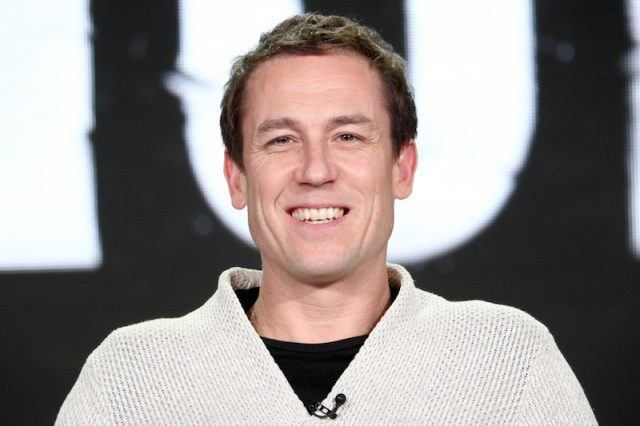 Tobias Menzie smiles as he sits on stage during a panel interview.