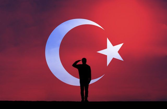 A Turkish soldier salutes in front of the flag.