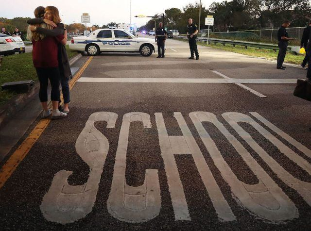 Two mourners hugging near the school.
