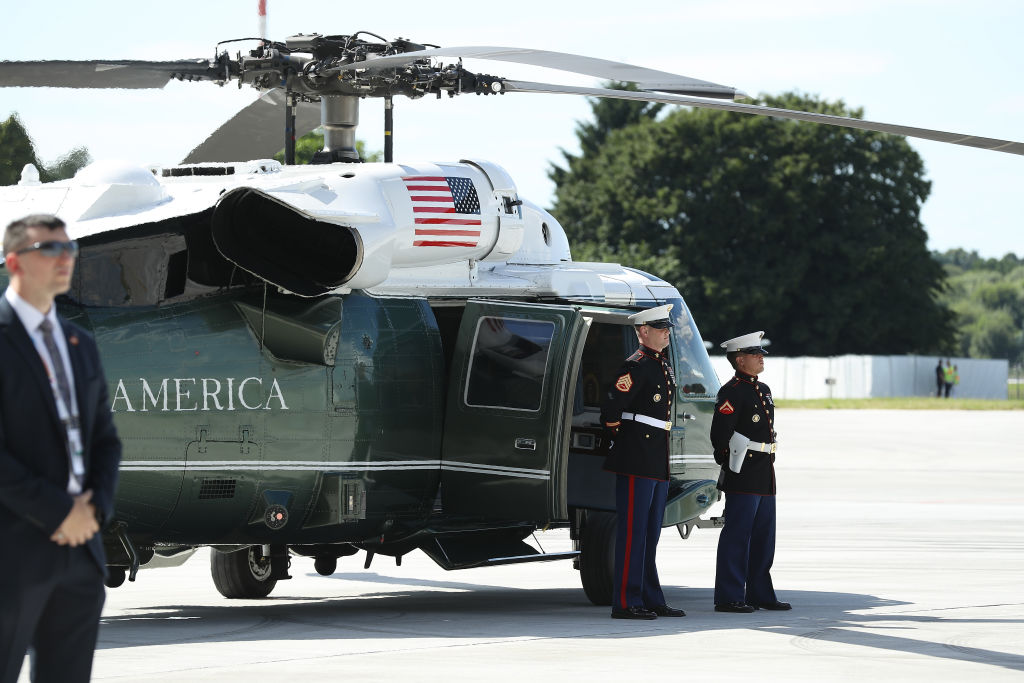 U.S. Marines and a member of the Secret Service stand near the helicopter