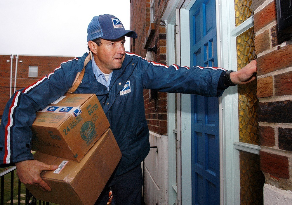 U.S. Postal Service carrier Ron Comly carries parcel packages