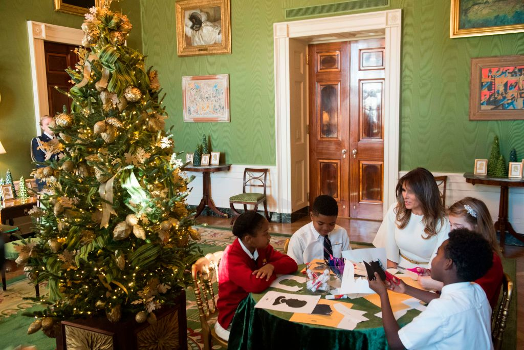 US First Lady Melania Trump speaks with children as they make holiday decorations in the Green Room