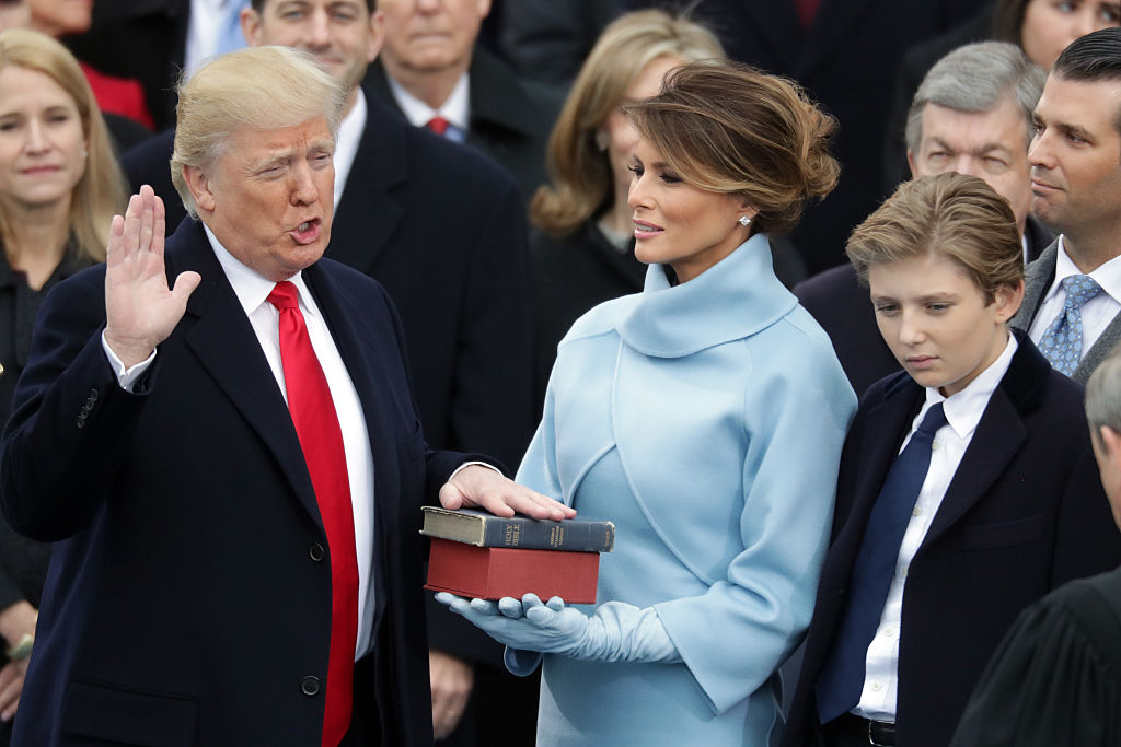 President Donald Trump takes the oath of office as his wife Melania Trump
