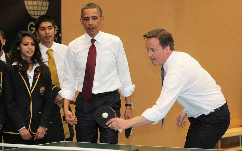 U.S. President Barack Obama plays table tennis with British Prime Minister David Cameron at Globe Academy school