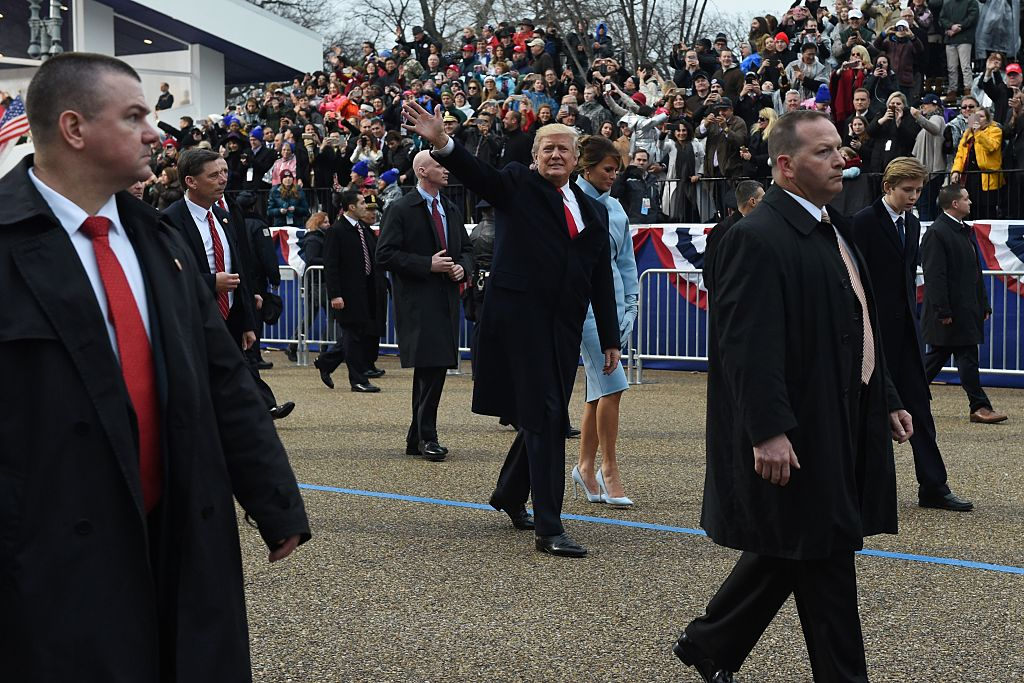 US President Donald Trump walks out of the car with his son Barron and wife Melania surrounded by Secret Service officers