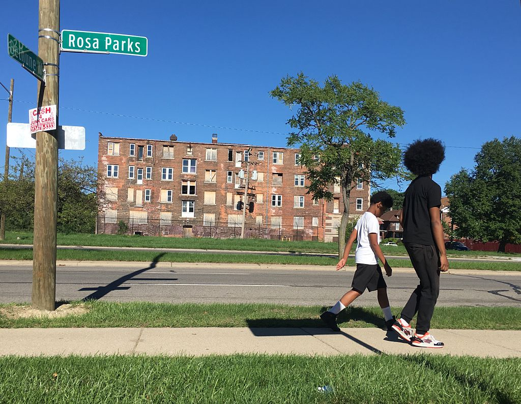 Two youths walk past a boarded up building on Rosa Parks Boulevard in Detroit, Michigan