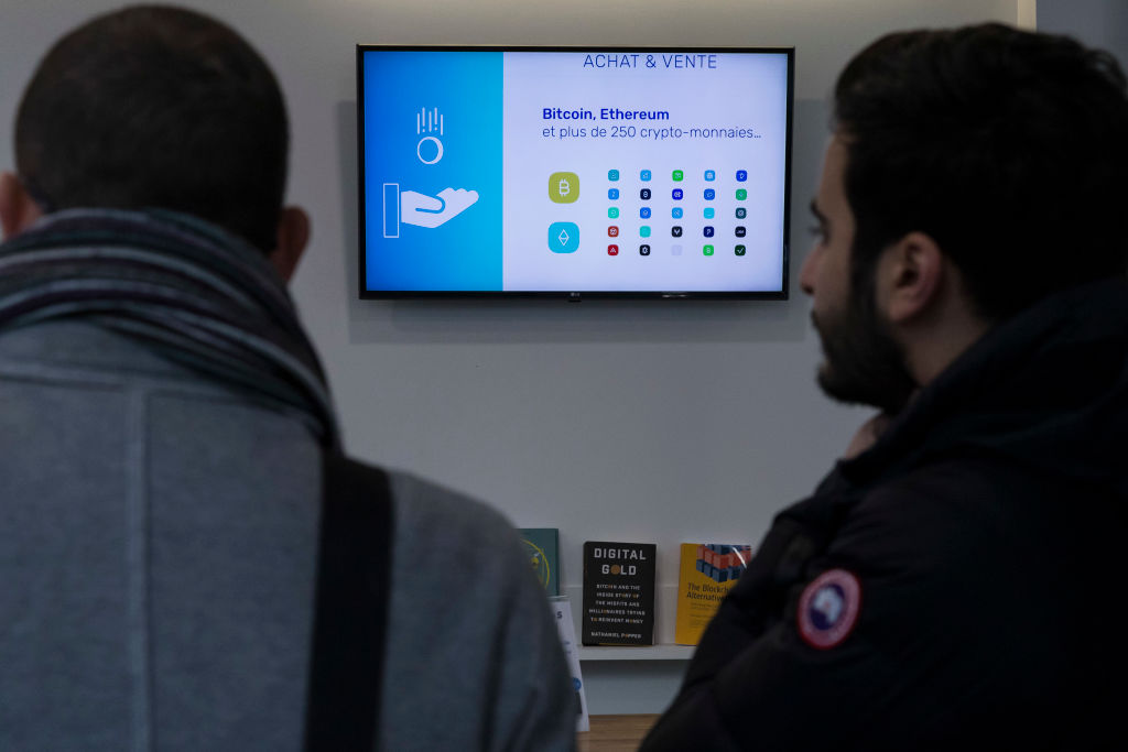 Men in line to buy bitcoin cryptocurrency