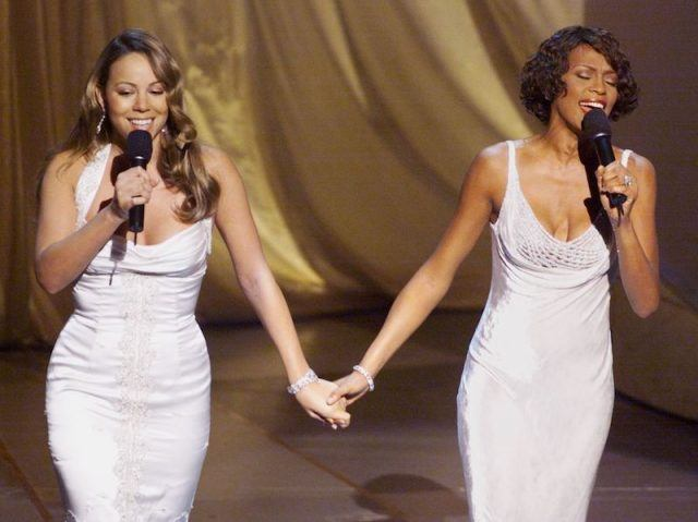 Mariah Carey and Whitney Houston performing on stage.