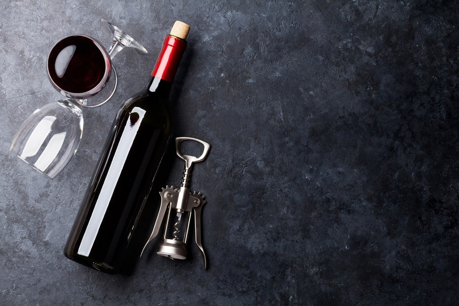 Red wine glasses and bottle on stone table. Top view with copy space