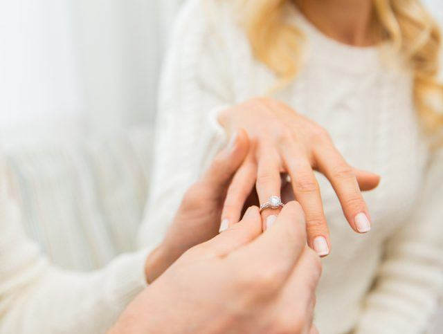 A woman holds up her hand as her partner inserts an engagement ring.