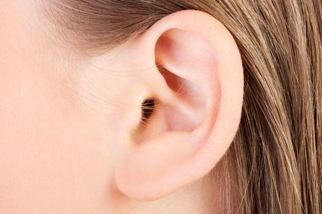 Close-up of a human ear of a person with blond hair.