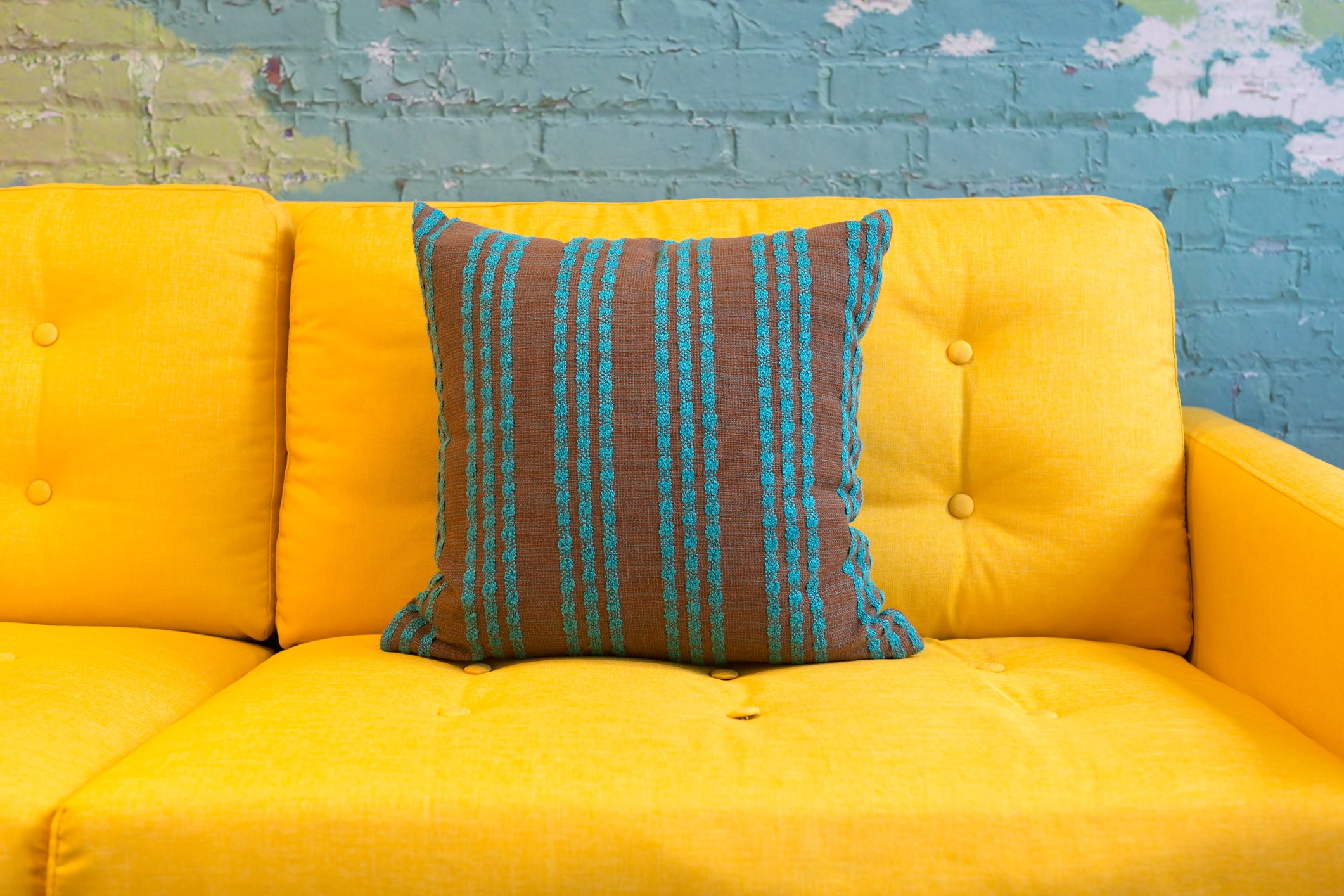Close up of yellow fabric sofa and cushions