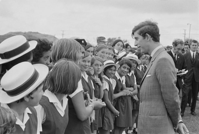 A young prince Charles interacts with a group of students.