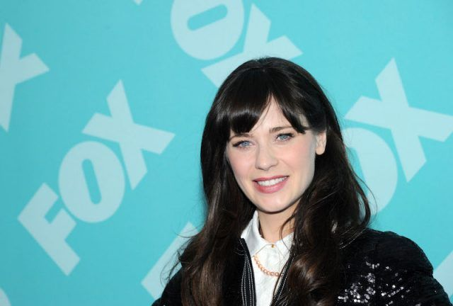 Zooey Deschanel smiling in front of a blue background.
