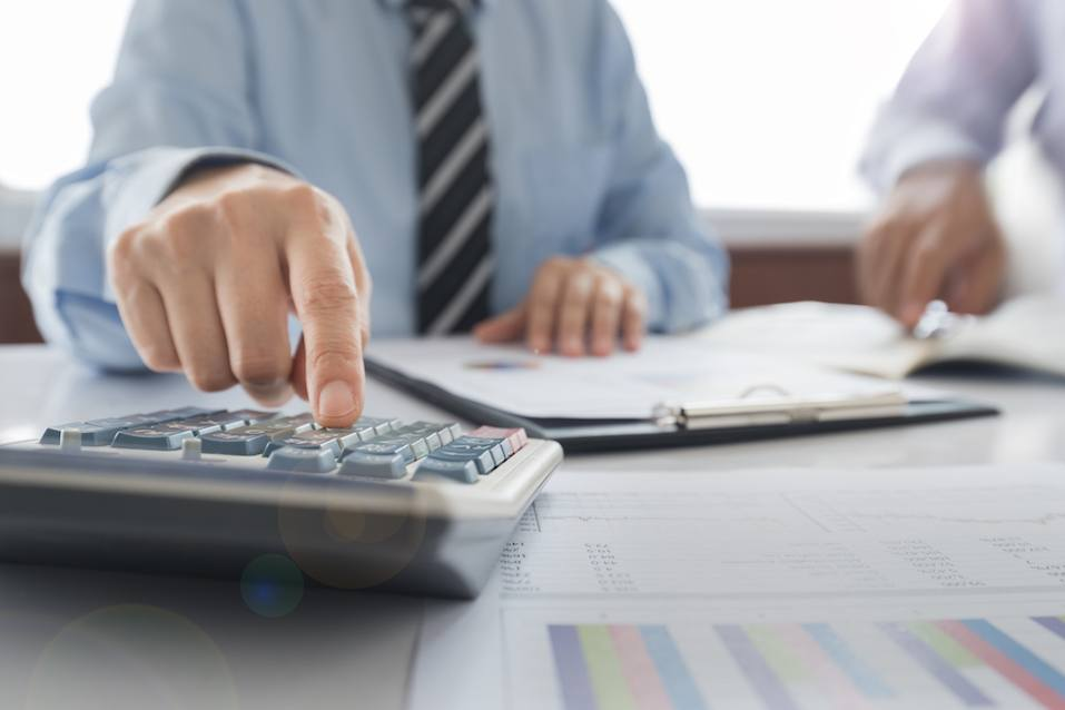 Businessman using a calculator to calculate the numbers.