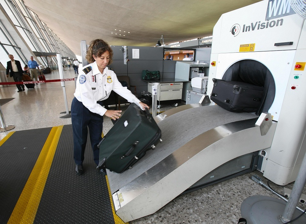 TSA Officer Beatriz Thompson processes airline passengers luggage thru an X-Ray machine
