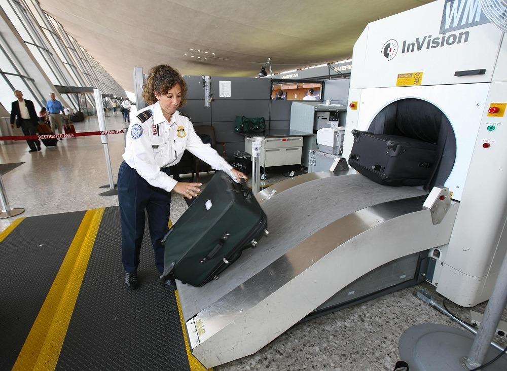 TSA Officer Beatriz Thompson processes airline passengers luggage thru an X-Ray machine