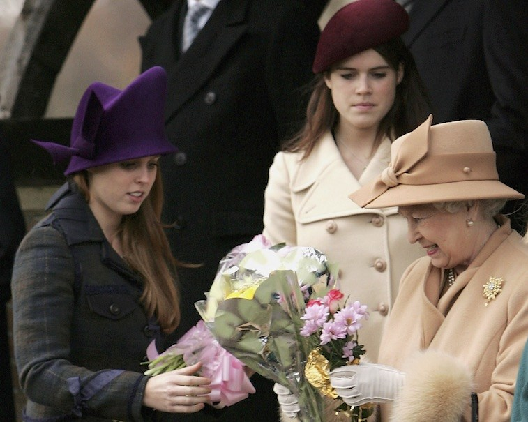 HM Queen Elizabeth II accepts bunches of flowers from well wishers and receives help from Britain's Princesses Beatrice and Eugenie as she leaves Sandringham Church after she attended the Christmas Day service on December 25, 2005 in Norfolk, England.